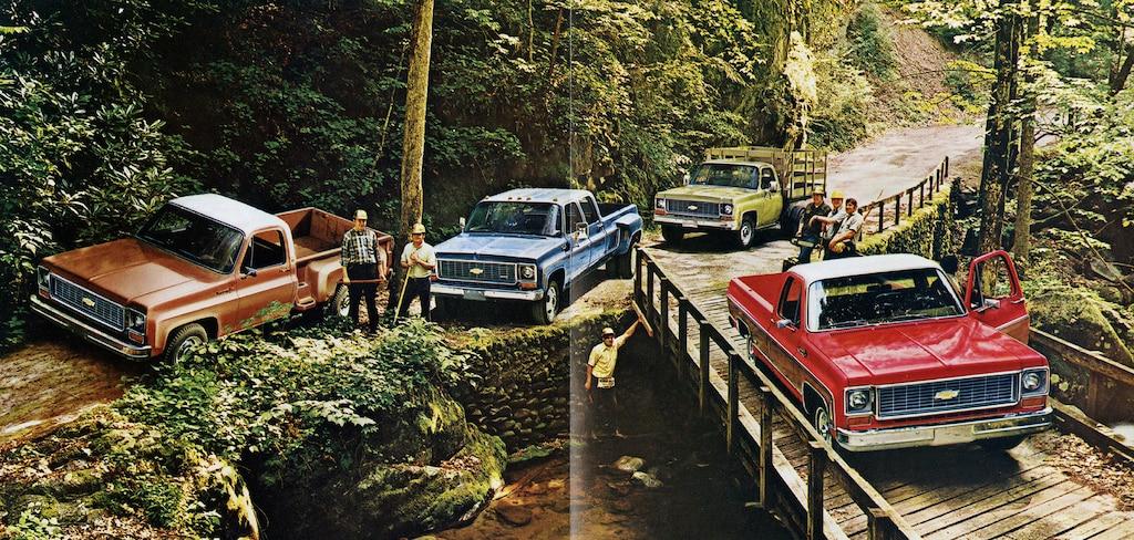 Una foto del folleto de camionetas Chevy del 1973 original con cuatro pickups de laserie C/K juntas en un camino de tierra y puente de madera junto a una colina empinada cubierta de árboles.