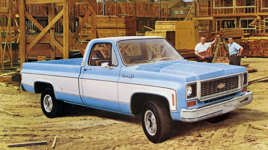 Una foto del folleto de camionetas Chevy del 1973 original con una pickup de laserie C/K en azul y blanco en un depósito de madera. Detrás de la camioneta hay dos hombres de pie.