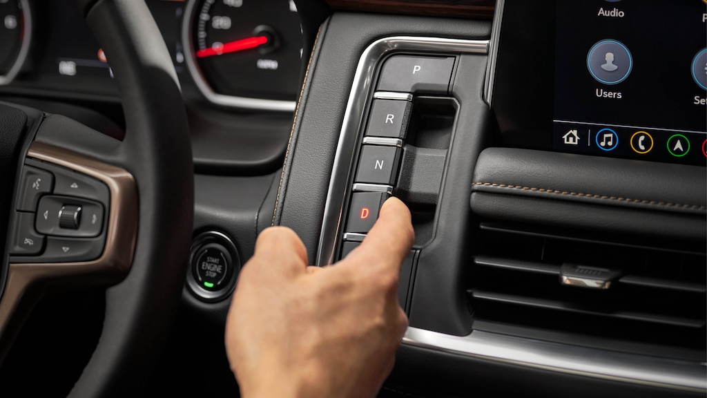 Un primer plano de la mano de una persona operando los controles de transmisión con botones en el panel de instrumentos de una Chevy Tahoe 2021.