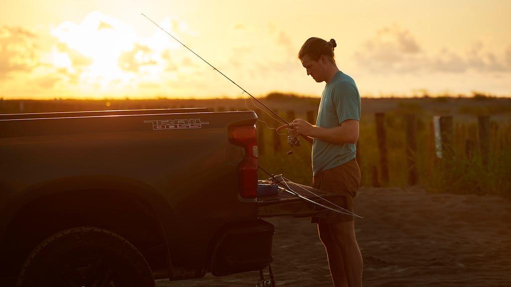 Un hombre con una remera y una gorra de béisbol hacia atrás se encuentra cerca de la puerta trasera abierta de una Chevy Silverado y está sosteniendo una caña de pescar, con el sol naciente de fondo.