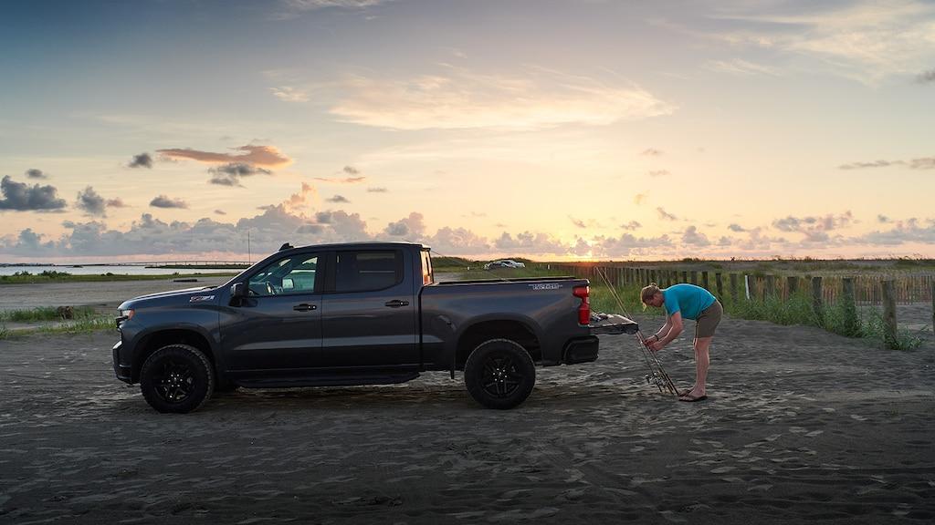 Un hombre se agacha para trabajar en las cañas de pescar que se encuentran contra la puerta trasera abierta de una Chevy Silverado, con el sol naciente en el fondo.