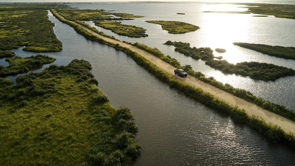Una vista aérea de una Silverado LT Trail Boss conduciendo por un camino de tierra entre dos áreas de remanso a lo largo de la costa.