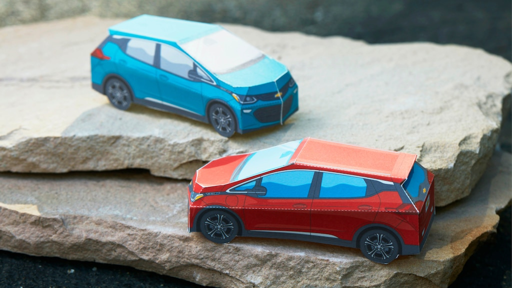 Modelos miniatura de papel del Bolt EV enRojo Cajún yAzul Oasis sobre una pila de rocas planas.