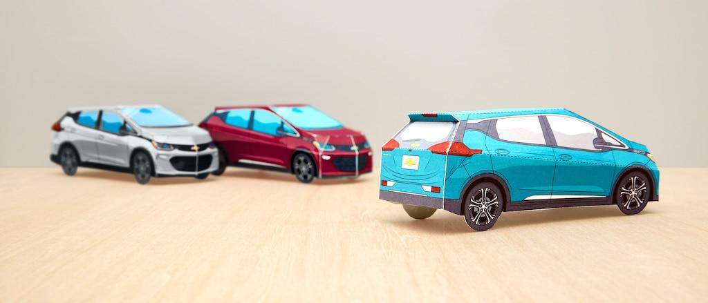 Tres modelos de papel terminados delBoltEV enPlata Hielo Metálico, Rojo Cajún y Azul Oasis sobre una mesa.