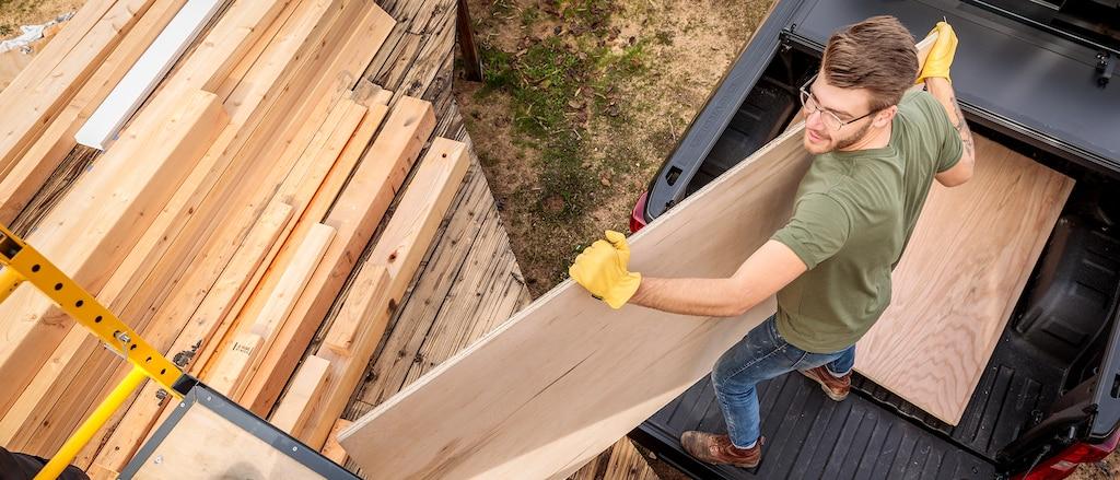 Visto desde arriba, un hombre con ropa de trabajo y guantes mueve láminas de madera contrachapada desde la caja de una camioneta pickup Chevy Silverado color Negro hacia una pila de madera cercana.