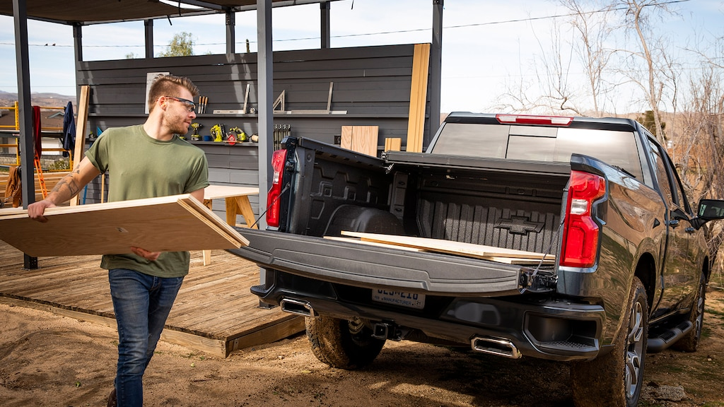 Un hombre con ropa de trabajo y gafas de seguridad carga láminas de madera contrachapada en la caja abierta de una camioneta pickup Chevy Silverado en Negro.