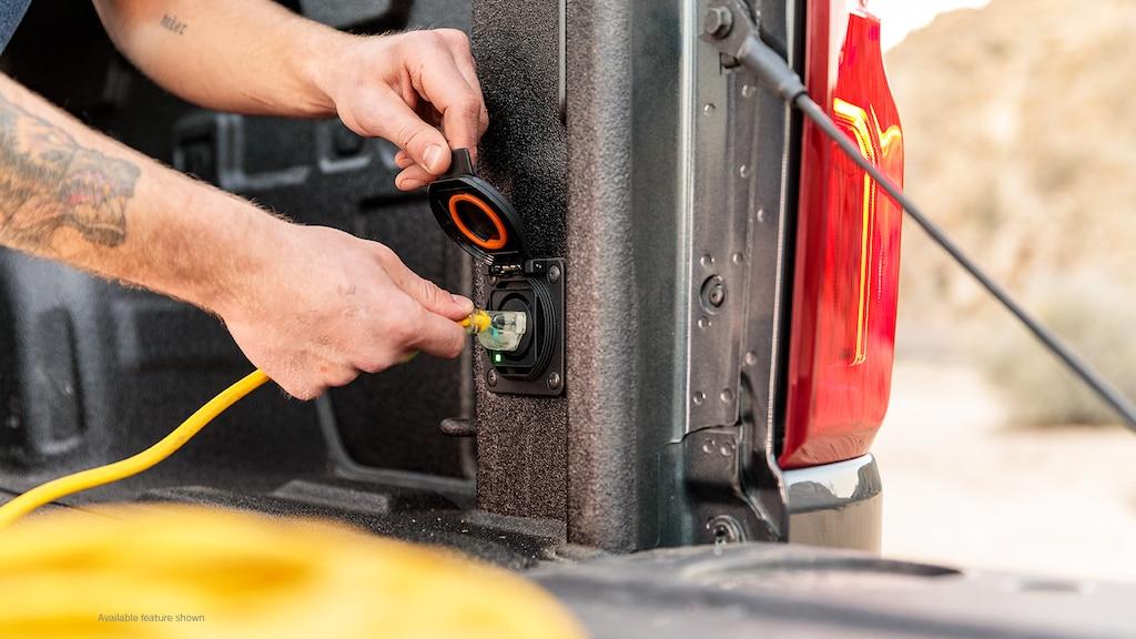 Se ven las manos de un hombre enchufando un cable de extensión amarillo en el enchufe de la parte trasera de la caja de una camioneta pickup Chevy Silverado en Negro.
