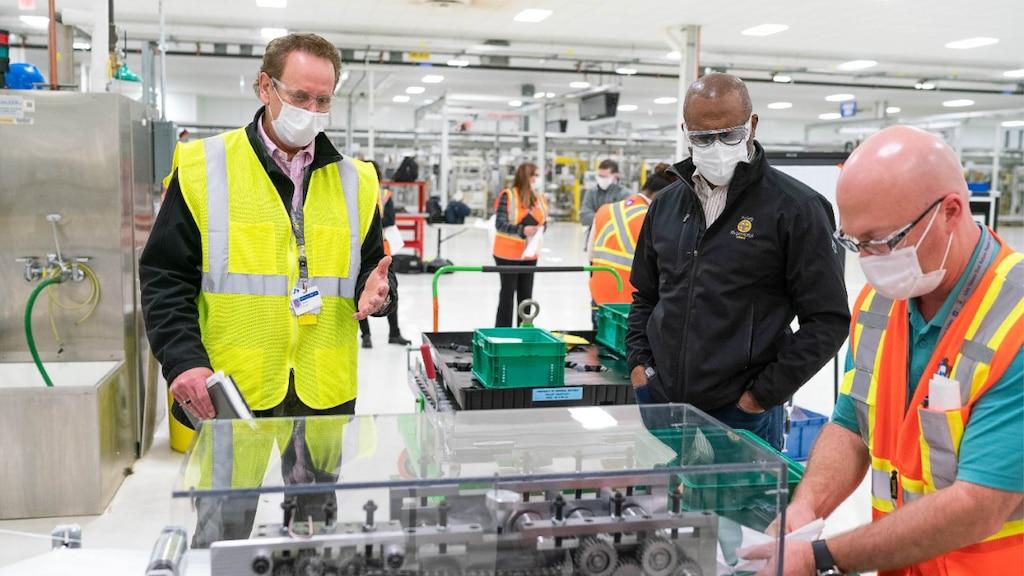 Tres hombres con mascarilla y chalecos de construcción reflectantes de pie alrededor de un equipo en una planta de producción. En el fondo se ve otra gente con chalecos de construcción.