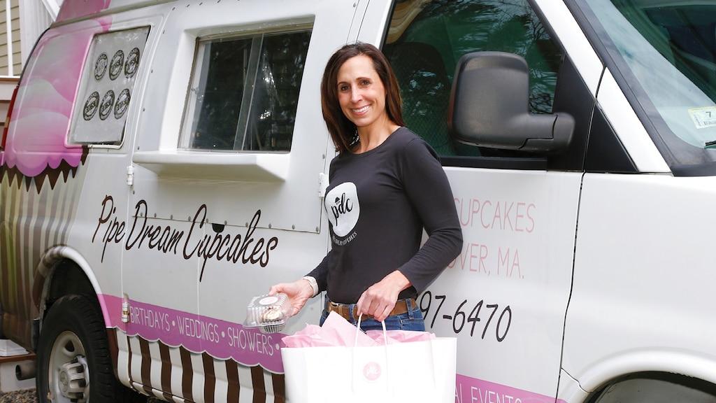 Nadine Levin de pie junto a su van Chevy Express adaptada con gráficos en rosado y negro de su negocio Pipe Dream Cupcakes.