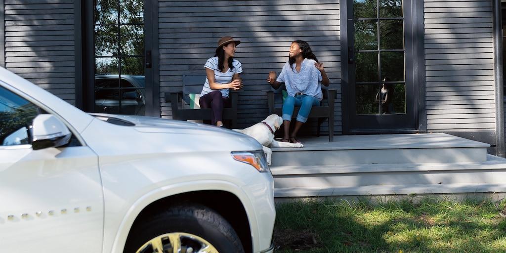 dos mujeres se sientan y conversan sobre el porche de una cabaña, con una Chevrolet Trverse color Blanco en el fondo.