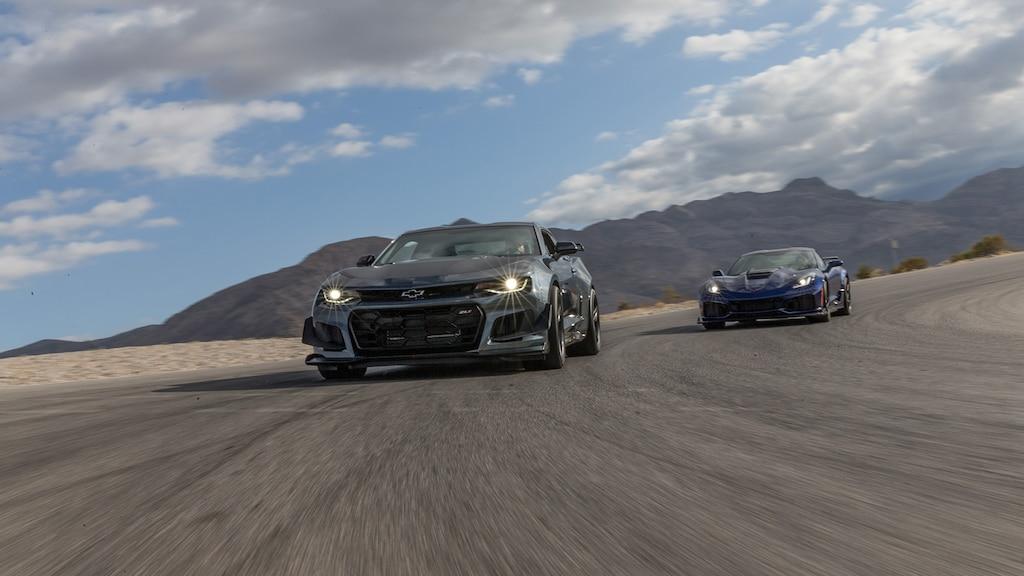 Una Camaro, con un Corvette detrás, en una pista de carreras en un centro privado en el desierto.
