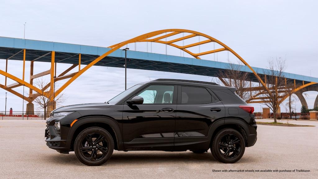 Una Trailblazer RS 2021 negra estacionada en un lote frente a un puente azul con arcos de soporte amarillos.