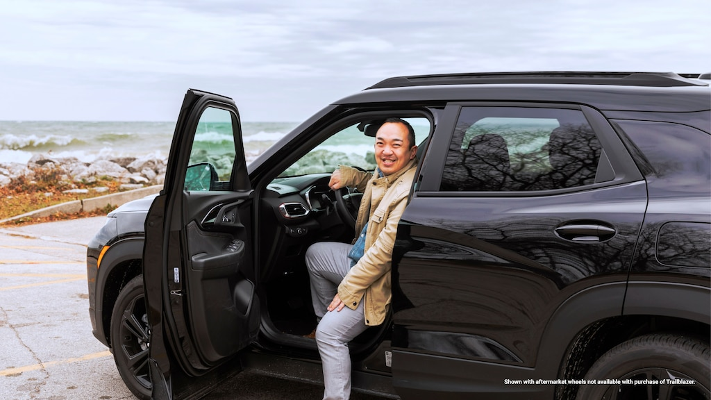 Erik Kennedy gira y sonríe a la cámara desde la ventanilla abierta del lado del conductor de su Trailblazer RS 2021 negra, que está estacionada en un lote con vista al lago Michigan.