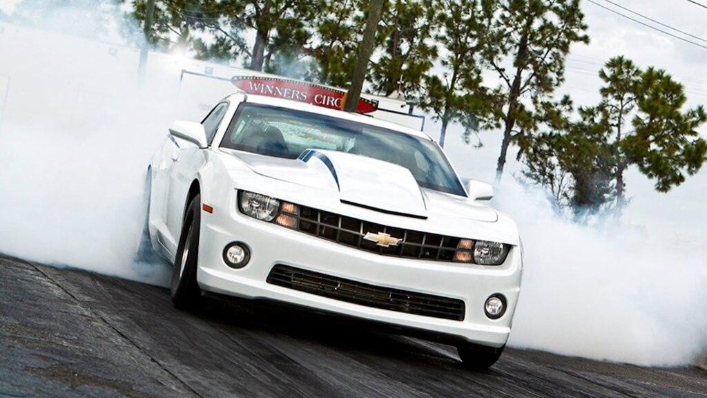 Un COPO Camaro blanco de quinta generación calentando rines en una pista, con humo saliendo de los neumáticos.