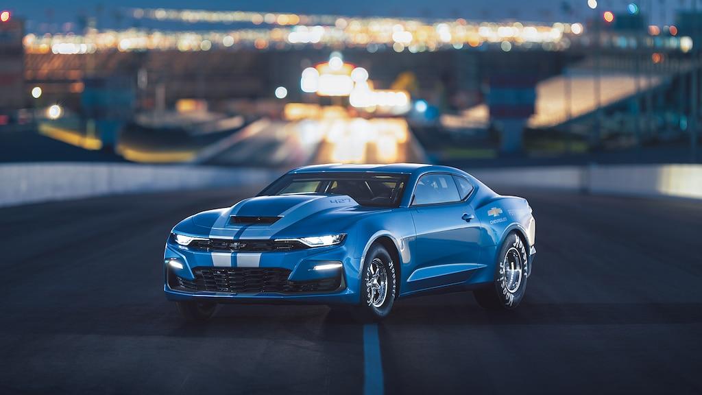 Un COPO Camar azul con motor V8 de 427 pulgadas cúbicas estacionado en una pista de carrera, con luces de fondo.
