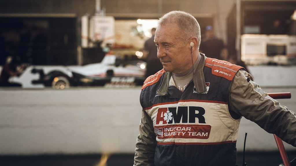 """Tim Baughman vistiendo un traje de seguridad con la leyenda """"AMR IndyCar Safety Team"""". Hay un auto de carreras y otros equipos de fondo."""