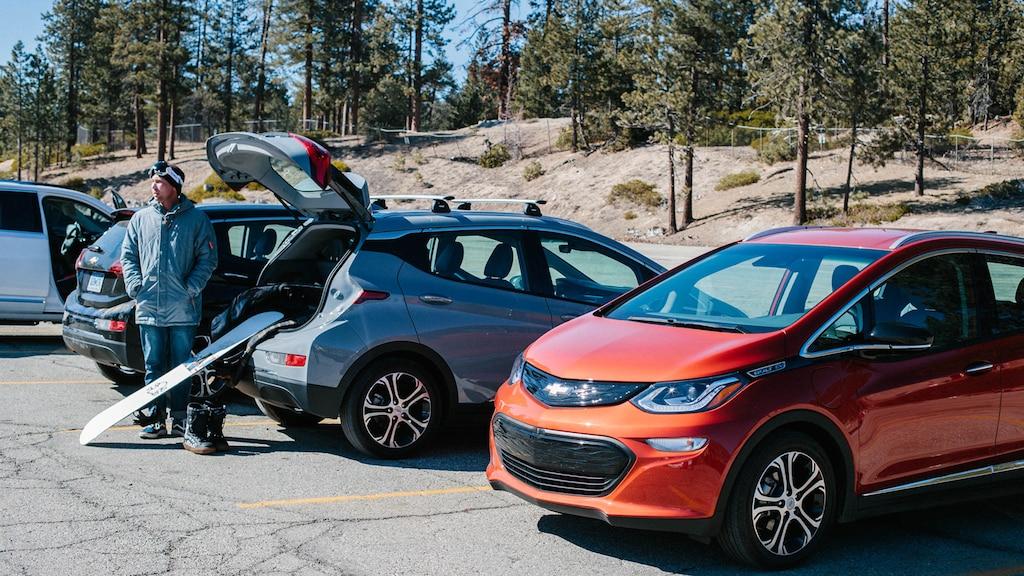 Una línea de Bolt EV en un estacionamiento en las montañas. Personas descargando una tabla de snowboard y otros equipos de la parte trasera de los Bolt EV.