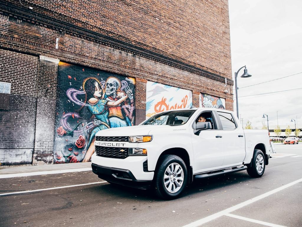 Freddy Diaz en una Silverado blanca en una calle de Detroit junto a uno de los coloridos murales de Freddy.