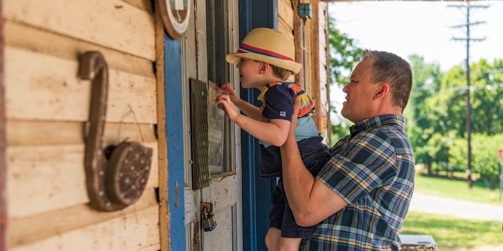 Un hombre que viste una camisa a cuadros alza a un niño pequeño para que pueda ver a través de una ventana en un edificio.