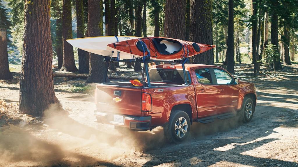 Una Chevy Colorado con dos kayaks en el portaequipajes conduce por el bosque.