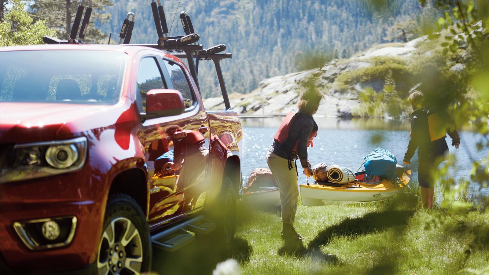 Dos aficionados al kayak descargan uno de la parte de atrás de una Chevy Colorado.
