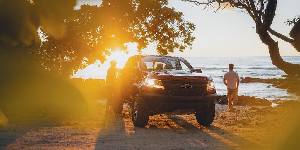 Una Chevrolet Colorado ZR2 roja estacionada en la playa al atardecer. Un hombre descansa apoyado en la camioneta mientras otro camina hacia el agua.