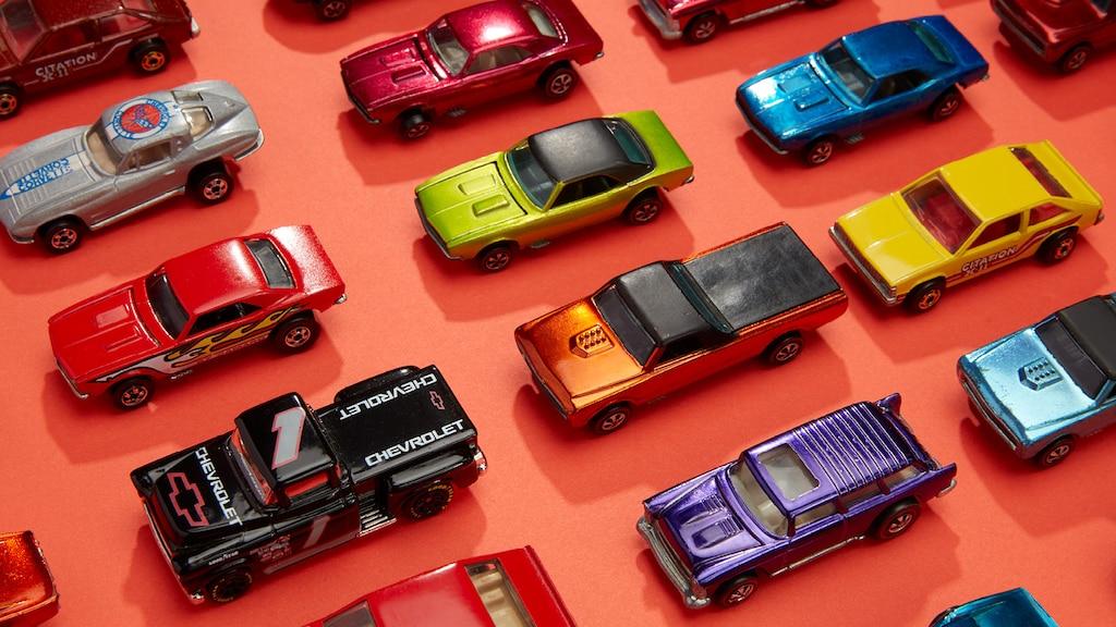 Hileras de autos Hot Wheels de diferentes tipos y colores alineados frente a un fondo naranja.