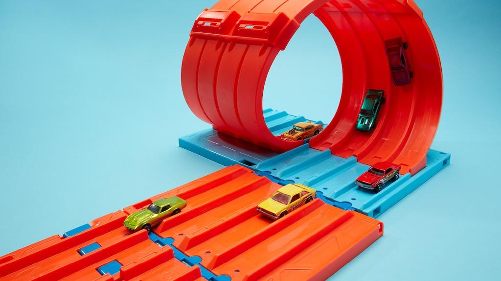 Varios Hot Wheels en una pista Hot Wheels naranja de cinco carriles con un bucle.