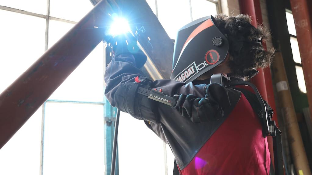 Una persona usando un exoesqueleto de alta tecnología y protector para el rostro suelda dos barras de hierro cruzadas frente a una ventana grande del tipo que se encuentran en depósitos.