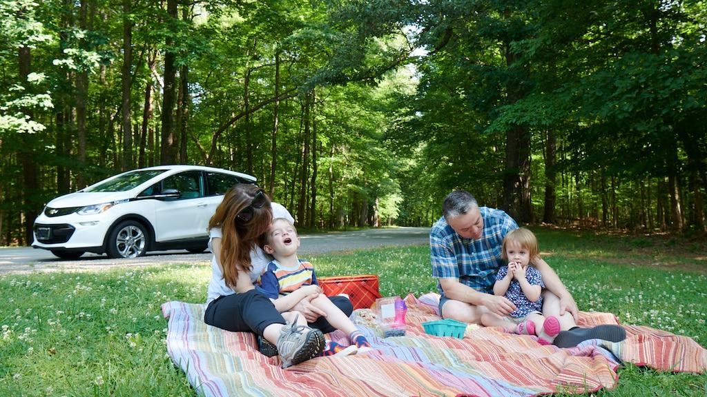 Un hombre y una mujer y dos niños están sentados sobre una manta colorida en el césped disfrutando un picnic, con un Bolt EV en blanco en el fondo.