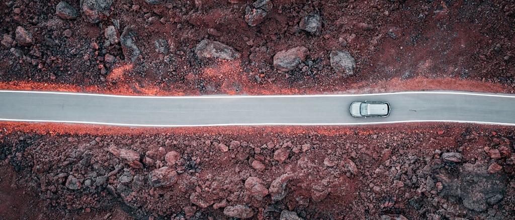 Una toma aérea desde un dron de una Chevrolet Blazer gris transitando un camino  negro a través de un campo de rocas de lava.