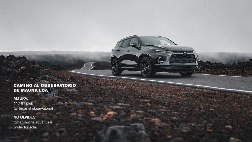 Una Chevrolet Blazer gris transitando una carretera que atraviesa un campo de rocas volcánicas negras.
