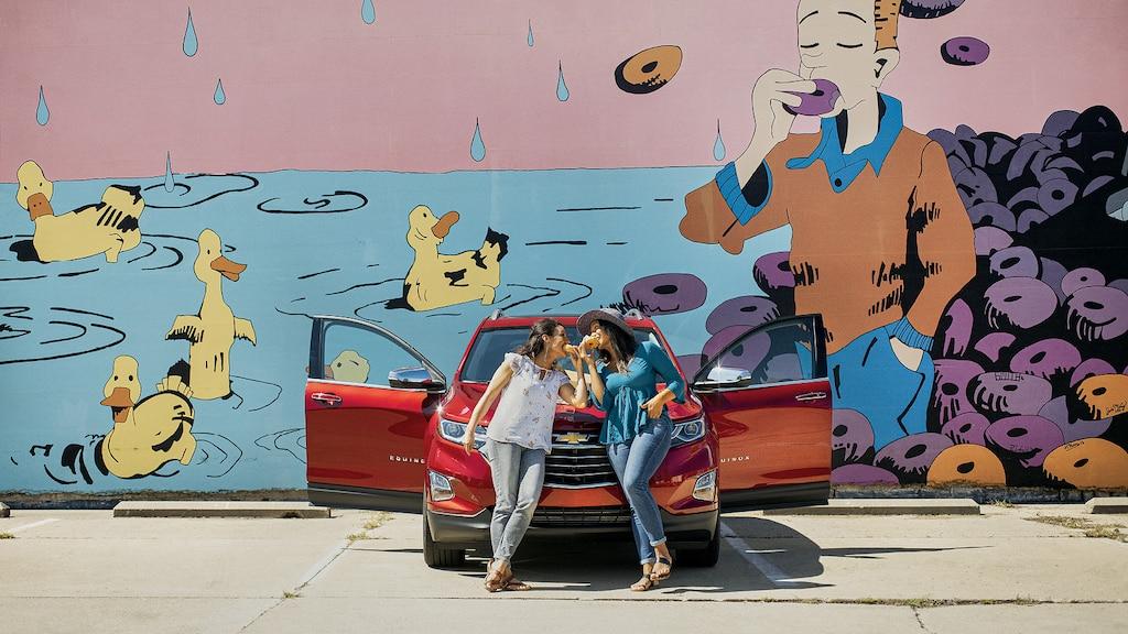 Dos mujeres apoyadas sobre el frente de una Chevrolet Equinox roja comiendo donas. Detrás de ellas hay un mural de un hombre comiendo una dona y patos nadando.