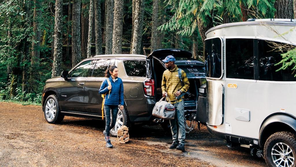 Una pareja joven con equipamiento para acampar, parados al lado de una Chevy Tahoe2021 con un remolque de viaje Airstream enganchado, estacionada entre árboles altos.