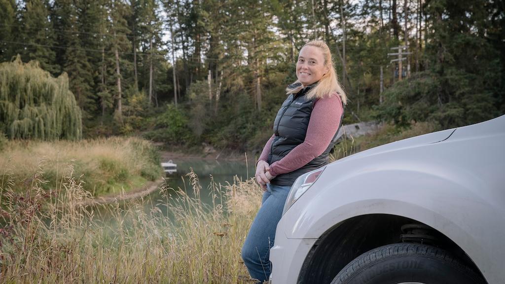 Jennifer, miembro de OnStar, apoyada sobre el frente de su camioneta con un campo y árboles en el fondo.