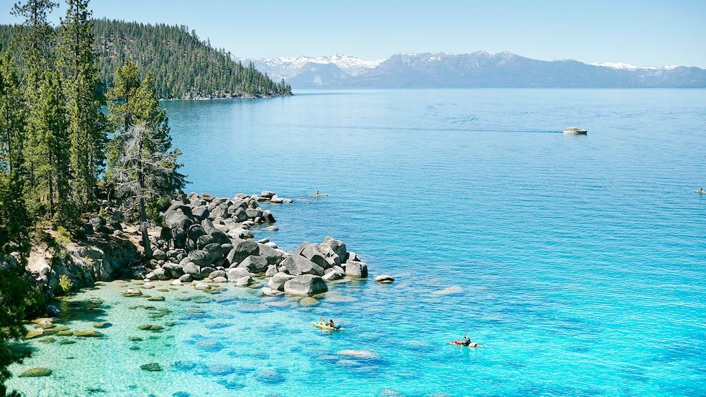 Un lago azul muy transparente con rocas y árboles en la costa y montañas a la distancia.