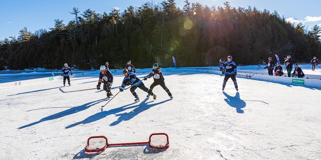 Un grupo de personas jugando al hockey sobre un estanque congelado, con un arco bajo al frente y árboles de fondo.