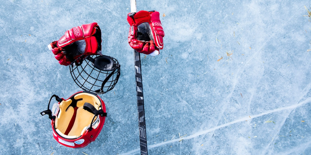 Un par de guantes de hockey, un casco, protección facial y un palo sobre el hielo.