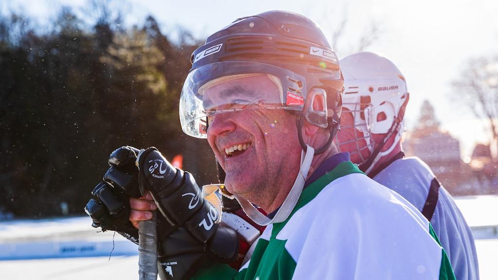 Un hombre con un casco y guantes de hockey que sostiene un palo de hockey y sonríe.