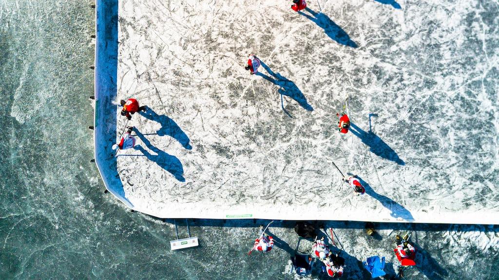 Vista aérea de un grupo de personas jugando al hockey en una cancha delimitada al aire libre.