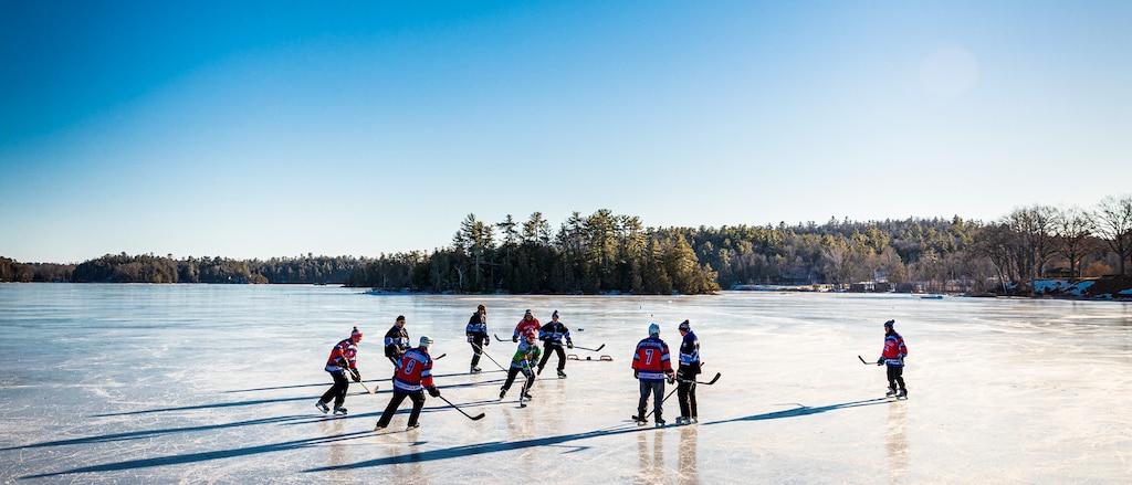 Un grupo de personas jugando al hockey sobre un estanque congelado, con un fondo arbolado y un cielo azul y despejado.