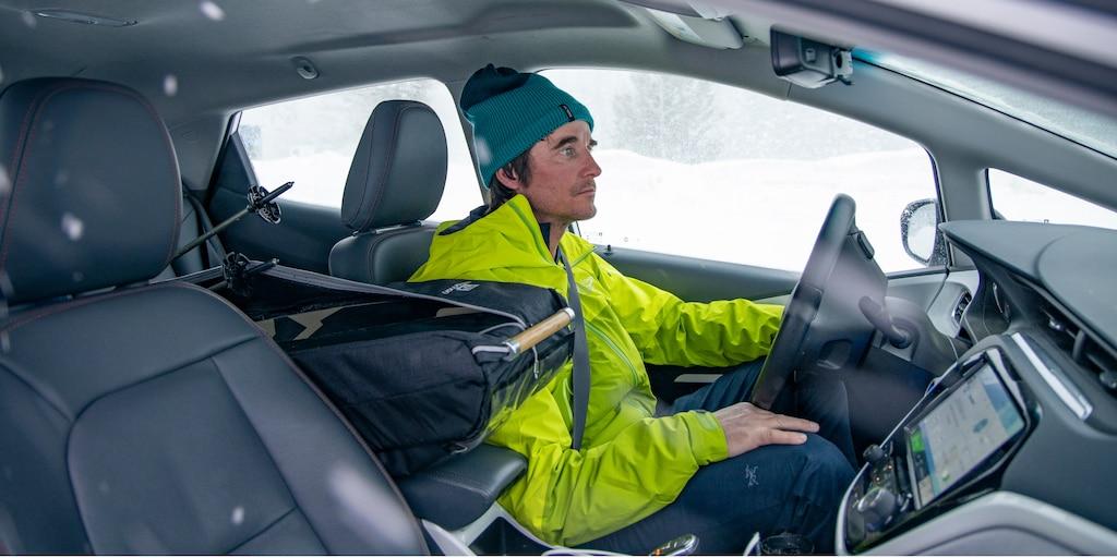 Greg Hill, con una chaqueta verde neón y una gorra turquesa, sentado en el asiento del conductor de un Bolt EV Blanco.