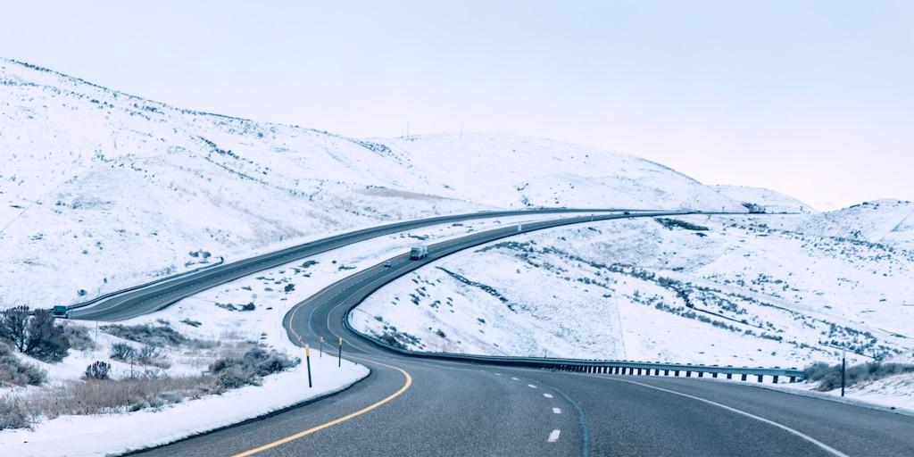 Una carretera de cuatro carriles dividida que serpentea a lo largo de colinas nevadas.