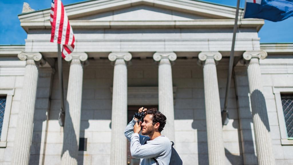 Un hombre con una cámara se encuentra en frente de las banderas y columnas del monumento de Bunker Hill.