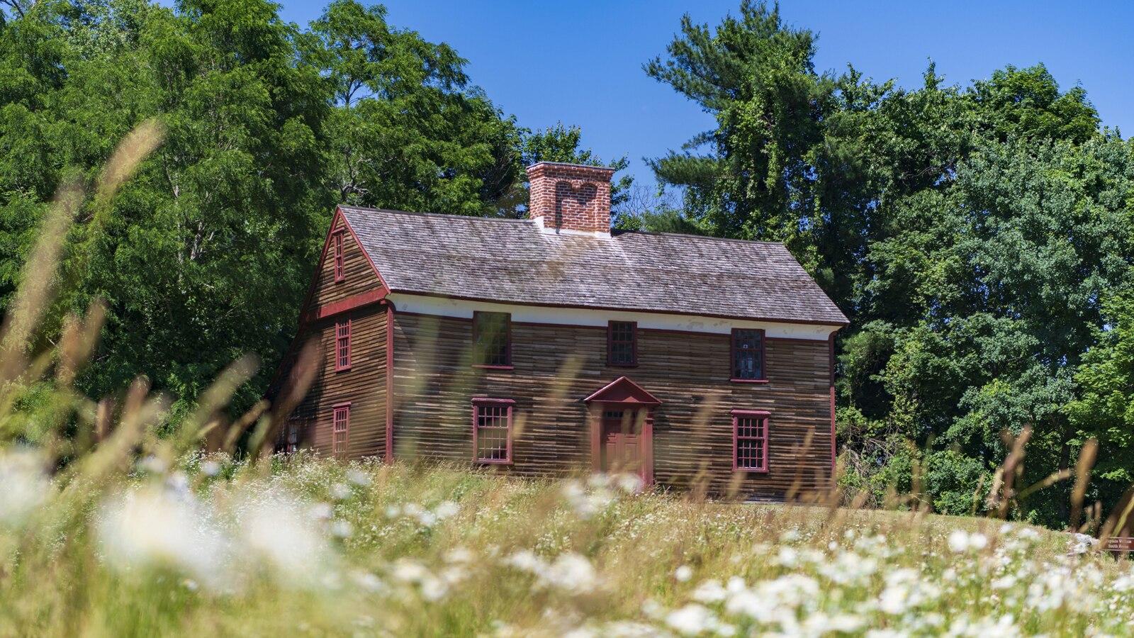 Una histórica casa de dos pisos con una fachada de madera oscura, rebordes rojos y una gran chimenea central.