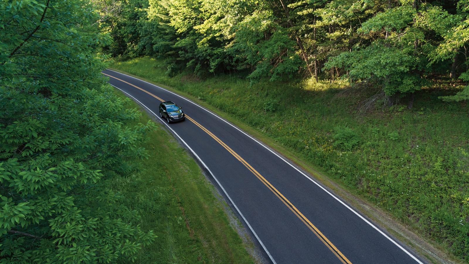 Una foto aérea lejana de una Equinox en un camino de dos carriles.