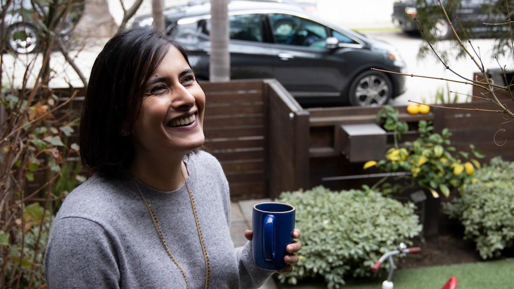 Una mujer sonriente está en el jardín sosteniendo una taza de café, con un Chevrolet Bolt EV color gris oscuro en la calle afuera del patio.