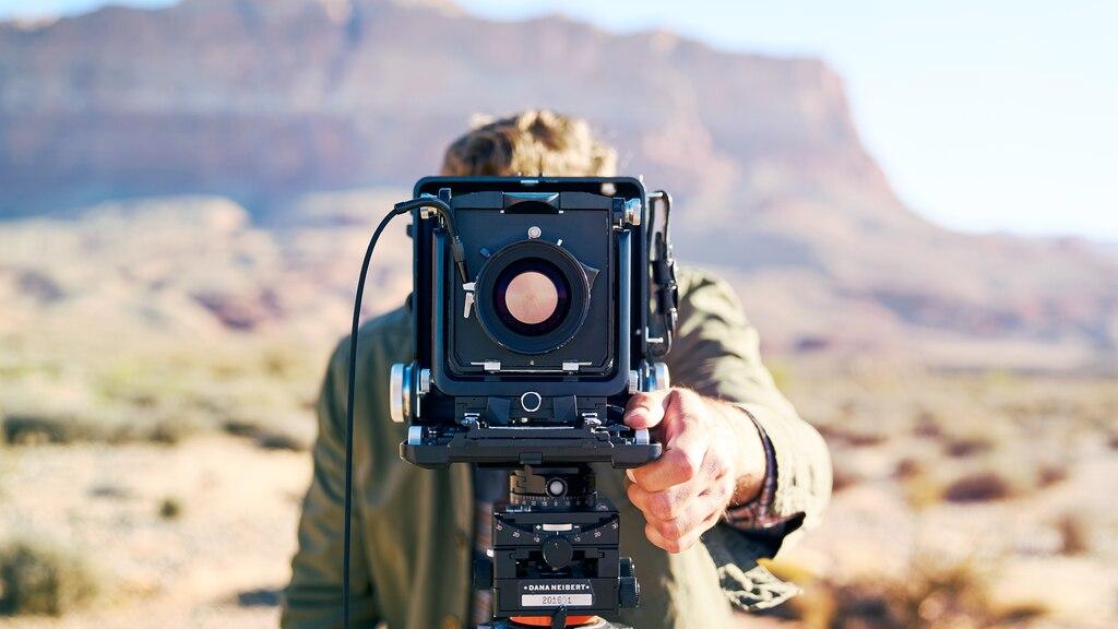 Persona parada detrás de una cámara de gran formato montada en un trípode con el desierto de Arizona y acantilados rocosos rojos a la distancia.