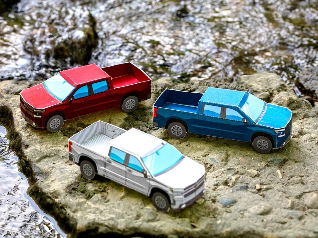 Modelos miniatura de papel de la Silverado RST 2020 diesel enRojo Cajún,Plata Hielo Metálico yAzul Cielo Norteño Metálico sobre un terreno rocoso.