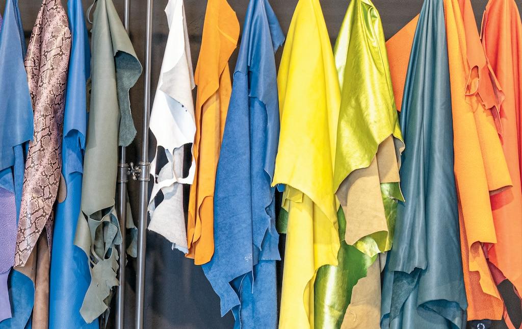 Una fila de telas de colores colgando de un exhibidor.
